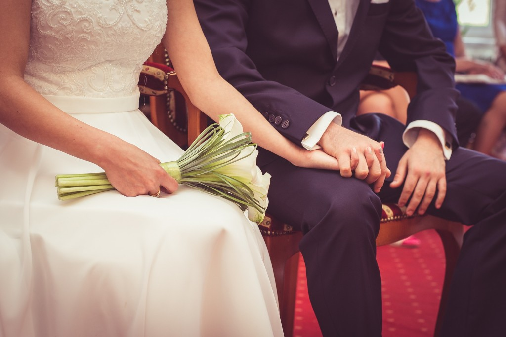 Bride and Groom seated hold hands