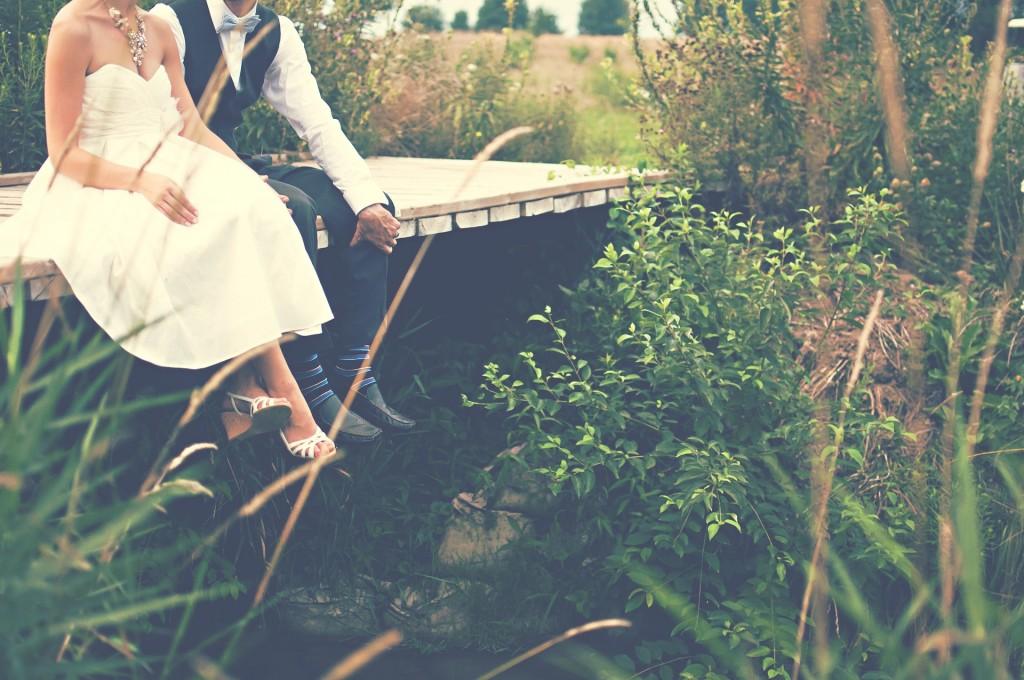 Bride and Groom sit on bridge over stream