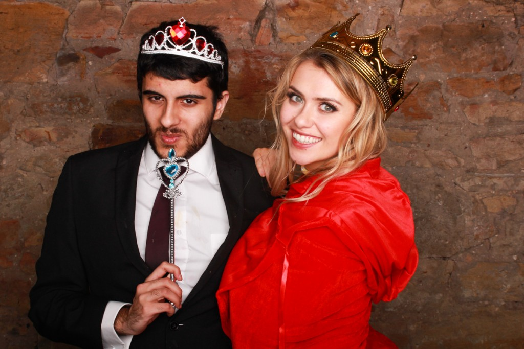 Man with tiara and women with crown in photo booth