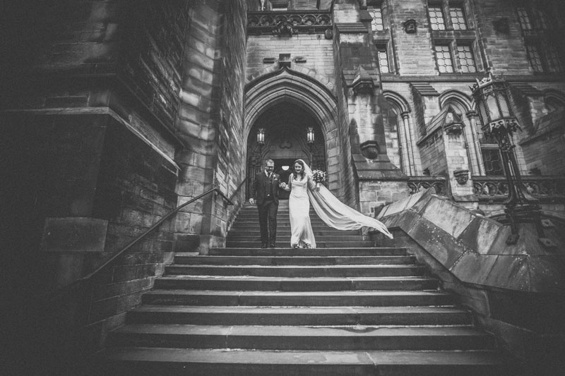 Bride & Groom walk down steps after ceremony at Glasgow University Memorial Chapel
