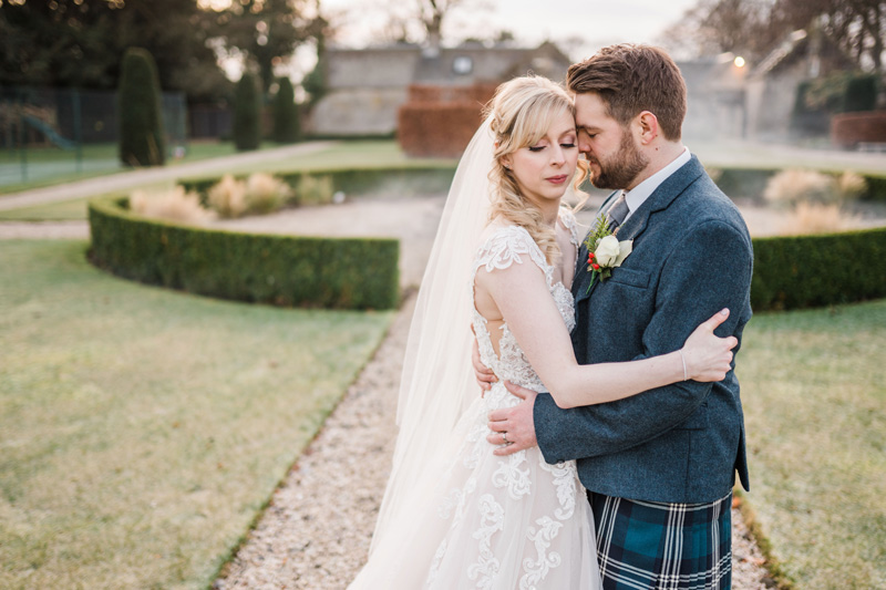 Bride and Groom embrace in gardens Carlowrie Castle Edinburgh