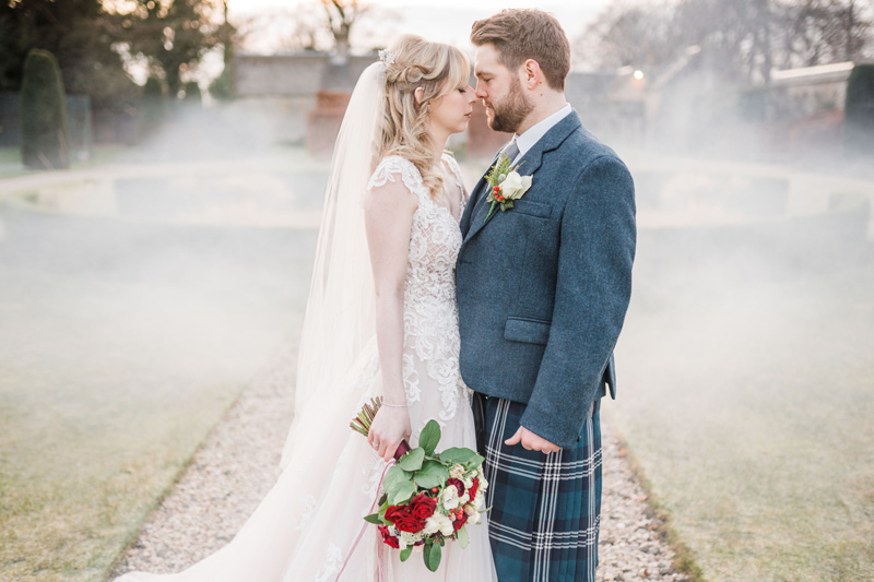 Bride and Groom stand outside Carlowrie Castle wedding in mist