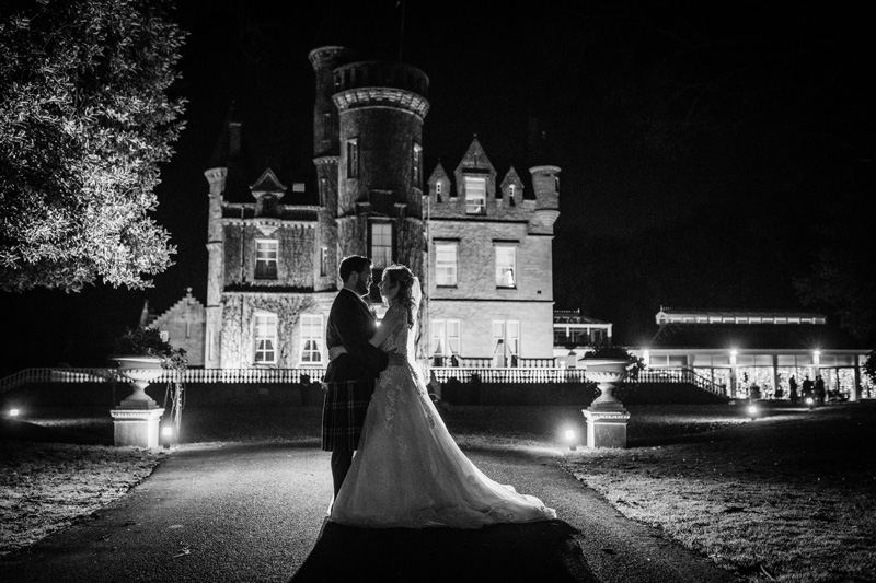 Bride and Groom stand outside Carlowrie Castle night black and white