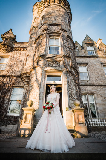 Bride in wedding dress and flowers standing outside Carlowrie Castle wedding