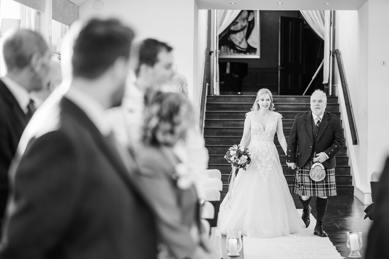Bride walking down the aisle with Father Carlowrie Castle wedding