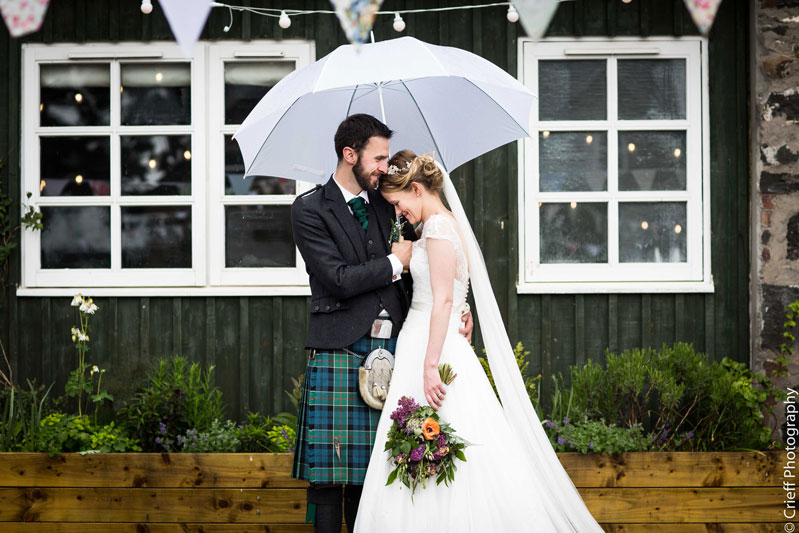Bride and Groom embrace under white umberella outside Comrie Croft Wedding Venue