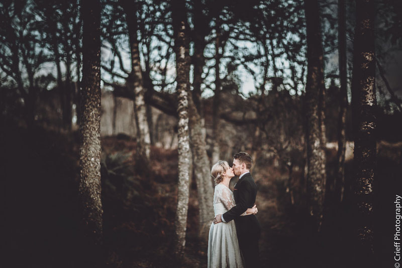 Bride and groom embrace in woodlands at Comrie Croft wedding