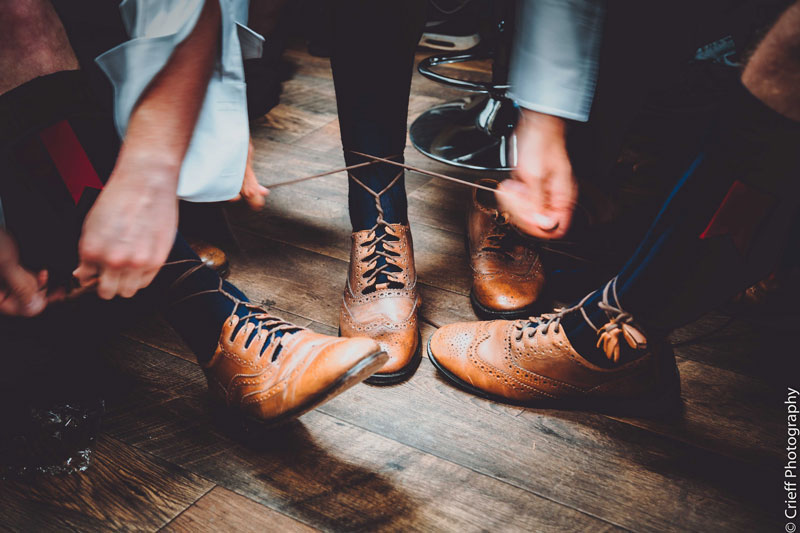 Groomsmen tie laces on Ghillie Brogues at Comrie Croft